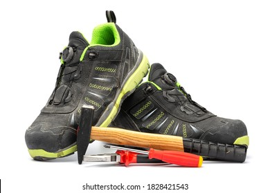 Pair of black safety shoes with green lining along with a hammer with wooden handle, a red pliers and a red Phillips screwdriver. With a white background.
