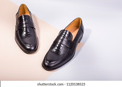 Pair black stylish loafers. Peach and white paper background. Poster for shoes store. Luxury shoes.