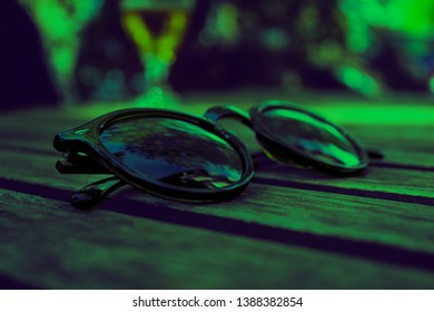 A pair of black sunglasses sat on a wooden table on a summery warm day