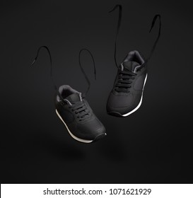 A pair of black unbranded sneakers floating in front of dark background.
