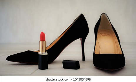 A pair of black velvet louboutin shoes and red lipstick