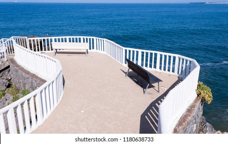 Pair of black and white benches overlooking the Cantabrian Sea in the village of Candas, Asturias, Spain.