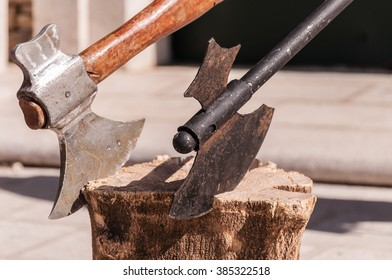 Pair of black and white hatchets on wood log