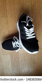 Pair of black and white shoes laying on the wooden floor. Time for lifestyle change, loose the weight, get fit and start over. It begins today, not tomorrow or next week. Symbol of what is going to be