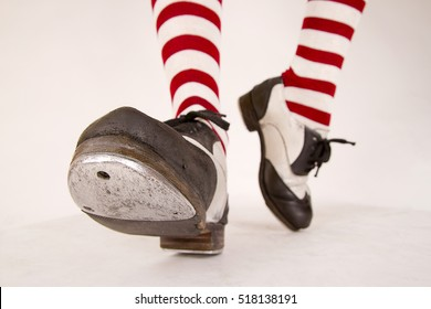 Pair of black and white tap shoes with red and white striped socks