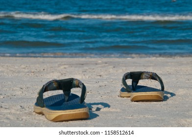 A Pair of Blue Flip Flops on the sand at the beach with the ocean waves in the background.  Copy space available