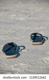 A pair of blue flip flops on the white sand beaches in florida, usa.  copy space available