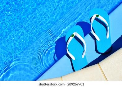 pair of blue flip-flops on the swimming pool