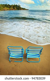 A pair of blue and green striped beach chairs close to the water on a beautiful, sandy beach.  There is a blue sky with clouds, green foliage and beautiful blue water of the ocean.