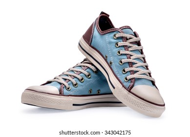 A pair of blue gumshoes with shoelace on a white background