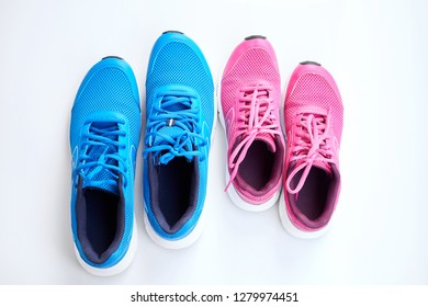 Pair of blue running sneakers for men and pair of pink one for women on white background. Concept love run. Run together. Family run. Top view.