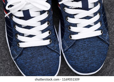 Pair of blue sneakers, closeup of white shoelaces