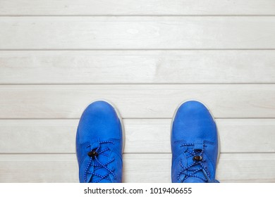 pair of blue sneakers on wooden background flat view