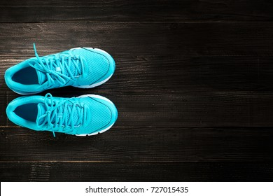 pair of blue sneakers on wooden background.