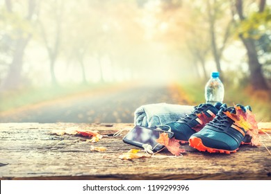 Pair of blue sport shoes smart phone and water laid on a wooden board in a tree autumn alley with maple leaves -  accessories for run exercise or workout activity.