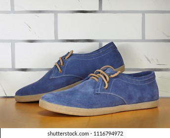 A pair of blue suede sneakers close up on the light brown exhibition shelf and white brick background.
