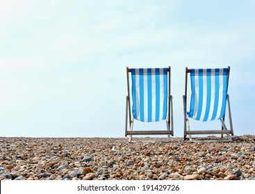 A pair of blue and white striped deck chairs on a pebbled beach, looking out to sea.