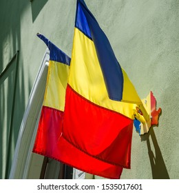 Pair of blue yellow red Romanian Flags mounted on the green wall facade of a government building in Romania, Europe. Two national flags incorporated on the stylized tricolor map of the country Romania