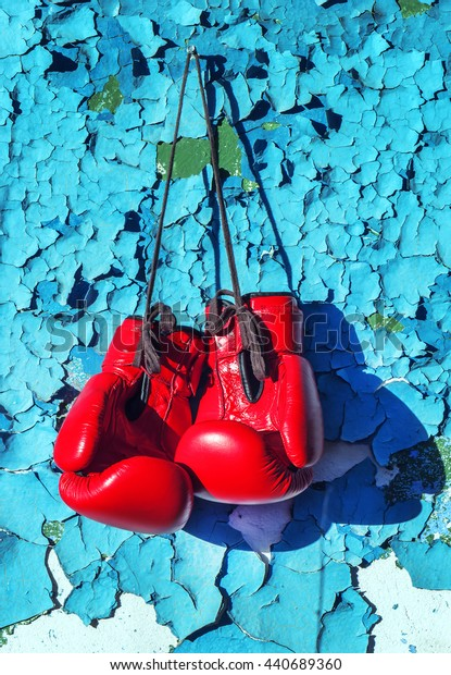 pair of boxing gloves hanging on the cracked wall