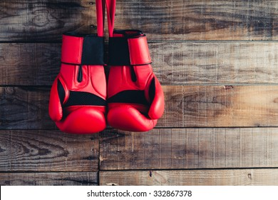 Pair of boxing gloves hanging in a rustic wooden wall.