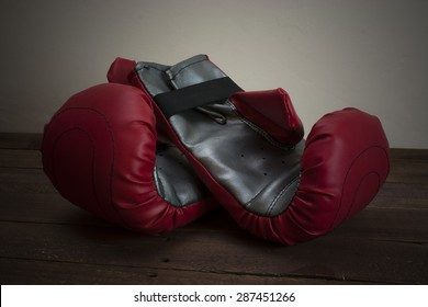 pair of boxing gloves on a wooden floor
