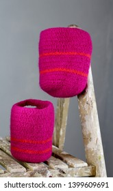 A pair of bright pink felted baskets with orange stripes on a wooden vintage ladder, a grey wall background , contemporary interior
