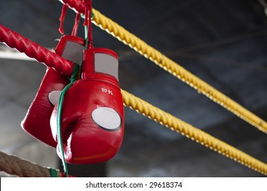 A pair of bright red Muay Thai boxing gloves hangs off the boxing ring in a slum camp