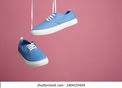 Pair of bright stylish shoes hanging against color background. Space for text