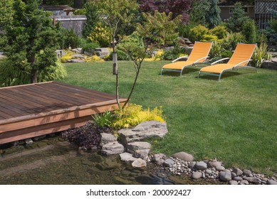 A pair of bright yellow designer lawn chairs invite you to relax in this beautifully landscaped backyard with deck spanning a creek in the foreground.