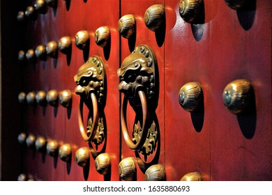 Pair of bronze Chinese Lion head door knockers on red Buddhist temple door in Chinatown Singapore in evening light and perspective view and soft focus