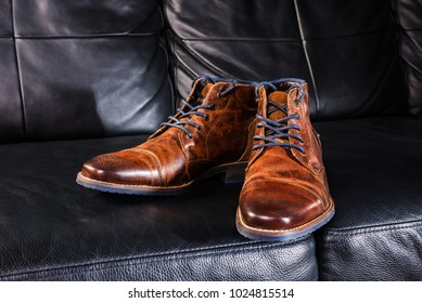 A pair of brown men's leather shoes placed on leather background