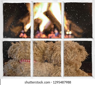 pair of brown teddy bears in front of fireplace snowflakes on windowpane