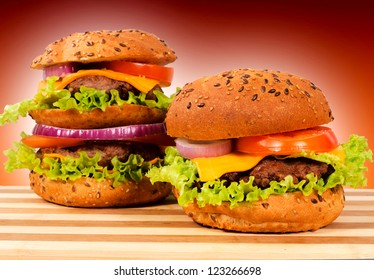 Pair of burgers on wooden board