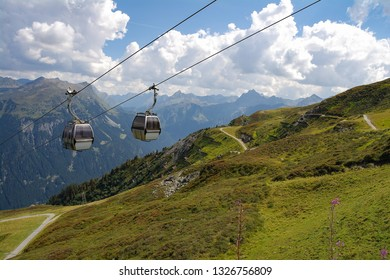 Pair of cable car view hanging over  green Austrian Alps in summer with sky background