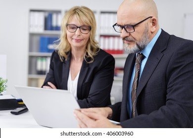 Pair of calm mature male and female co-workers dressed professionally in suit jackets discussing something on calendar in small office