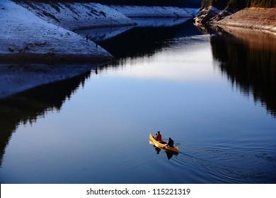Pair canoeing on almost frozen lake on winter (Belis lake, Transylvania, Romania)