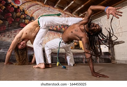 Pair of capoeira performers doing a kicking demonstration