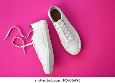 Pair of casual shoes on color background