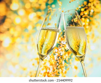 a pair of champagne flutes with golden bubbles make cheers on golden light background with space for text
