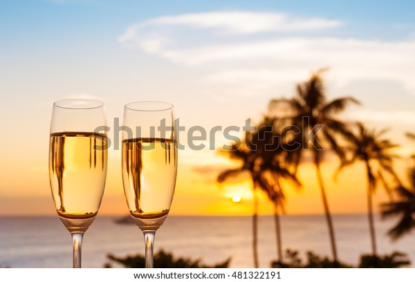 Pair of champagne glasses against a beautiful tropical sunset.