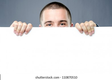 Pair of cheerful eyes  protrudes behind blank white board