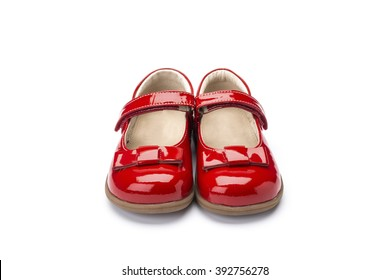 Pair of childs shiny red patent leather shoe with bow design and strap shot at a 3/4 angle on a white background