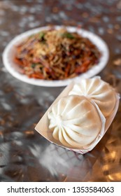 Pair of Chinese baozi dumplings with a chow mien noodle dish in the background, in a restaurant menu item combo