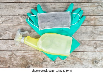 Pair of cleaning gloves, sanitizer spra and face mask on wooden table