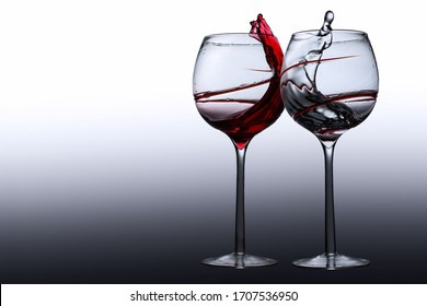 A pair of clinking wine glasses with red wine and water splashing inside