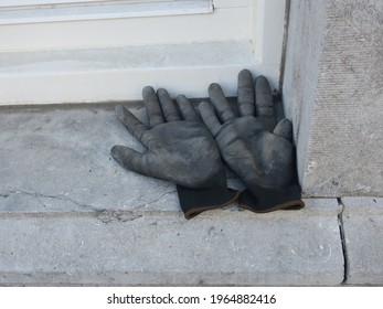 a pair of clothing gray black hand shoes laying on a stone windowsill