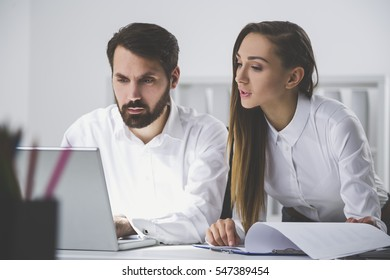 Pair of colleagues in white shirts at work. He is typing. She is looking at his laptop screen and pointing with her finger at a line in her report