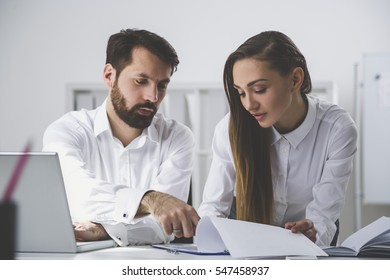 Pair of colleagues are working in a white office. He is showing her a line in a report. She is looking at it. Concept of collaboration