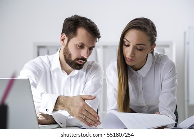 Pair of colleagues are working in a white office. He is showing her a line in a document. She is looking at it. Concept of collaboration