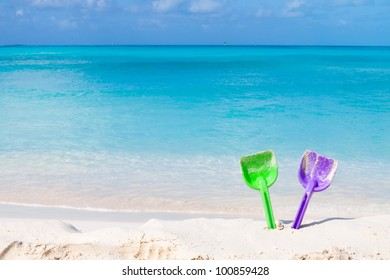 Pair of colored spades on a white sand beach in front of the sea. The right place for relaxation and vacations